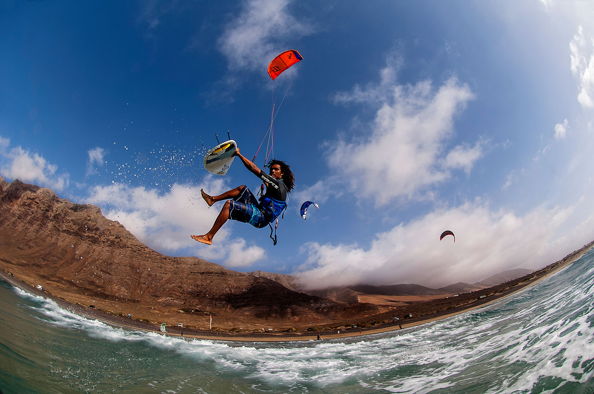 Kite boarders with a white board and red kite off the coast of Lanzarote catching air.