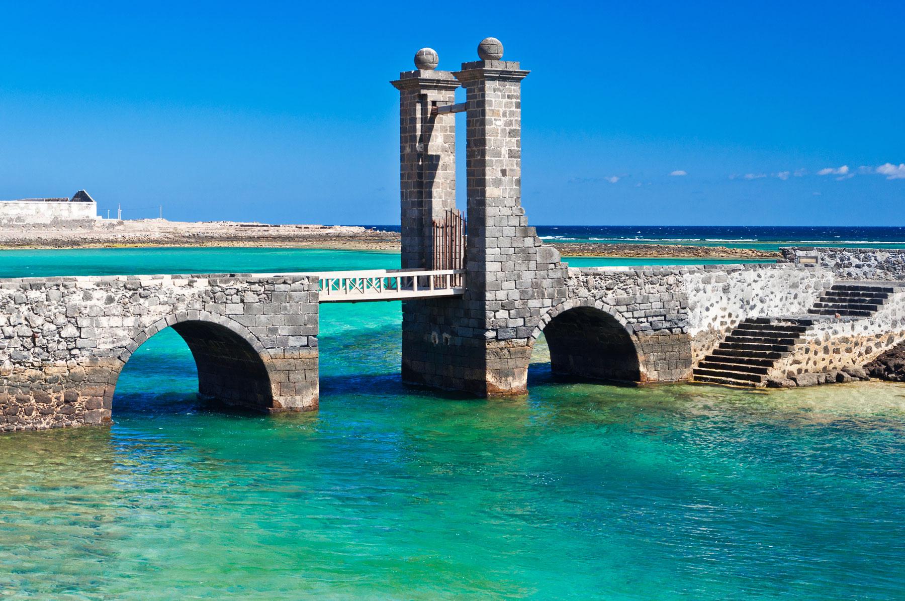 Old stone bridge over stunning blue ocean to Castle San Gabriel Arrecife Lanzarote