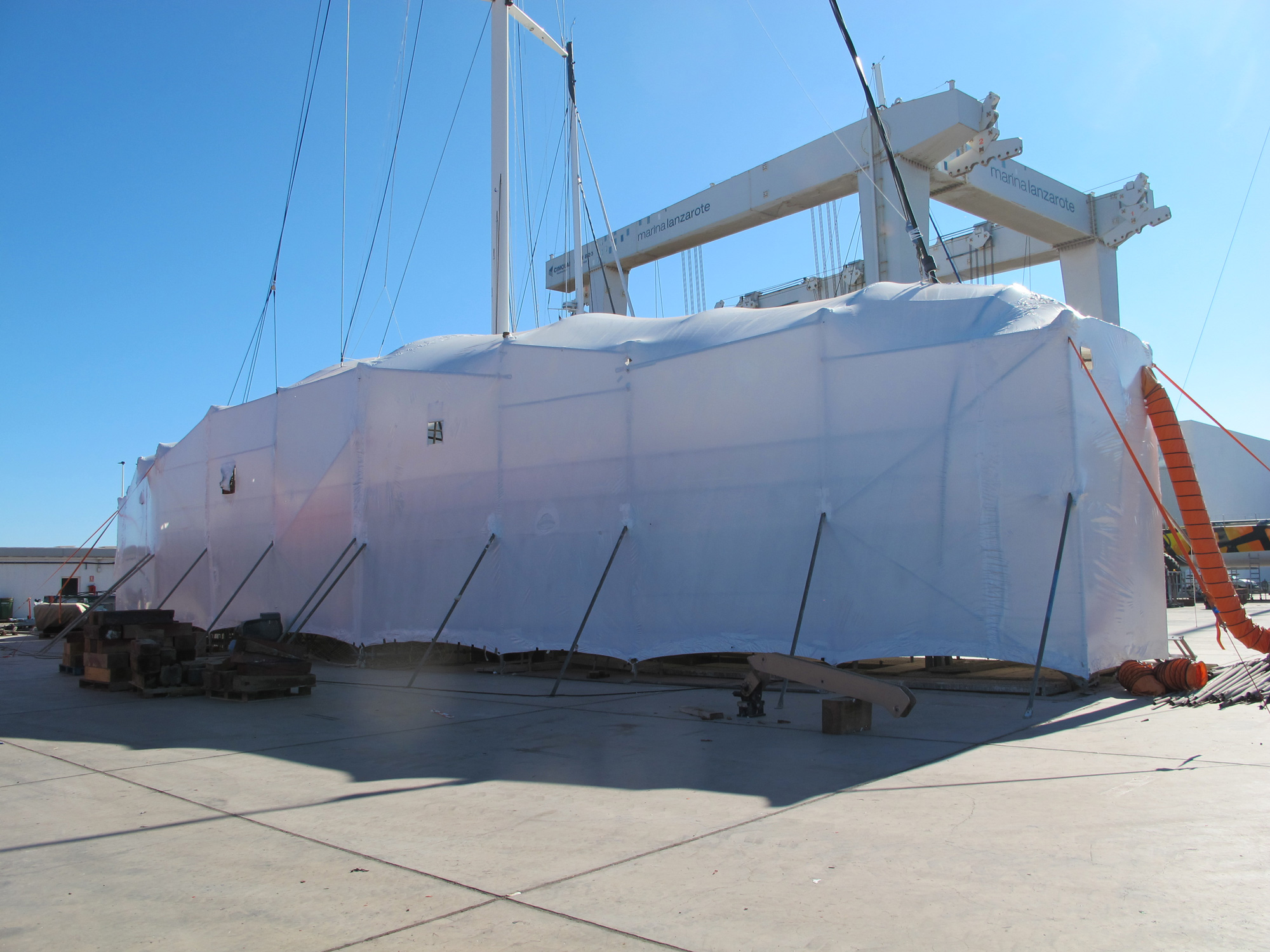 Large yacht covered in white wrapping.