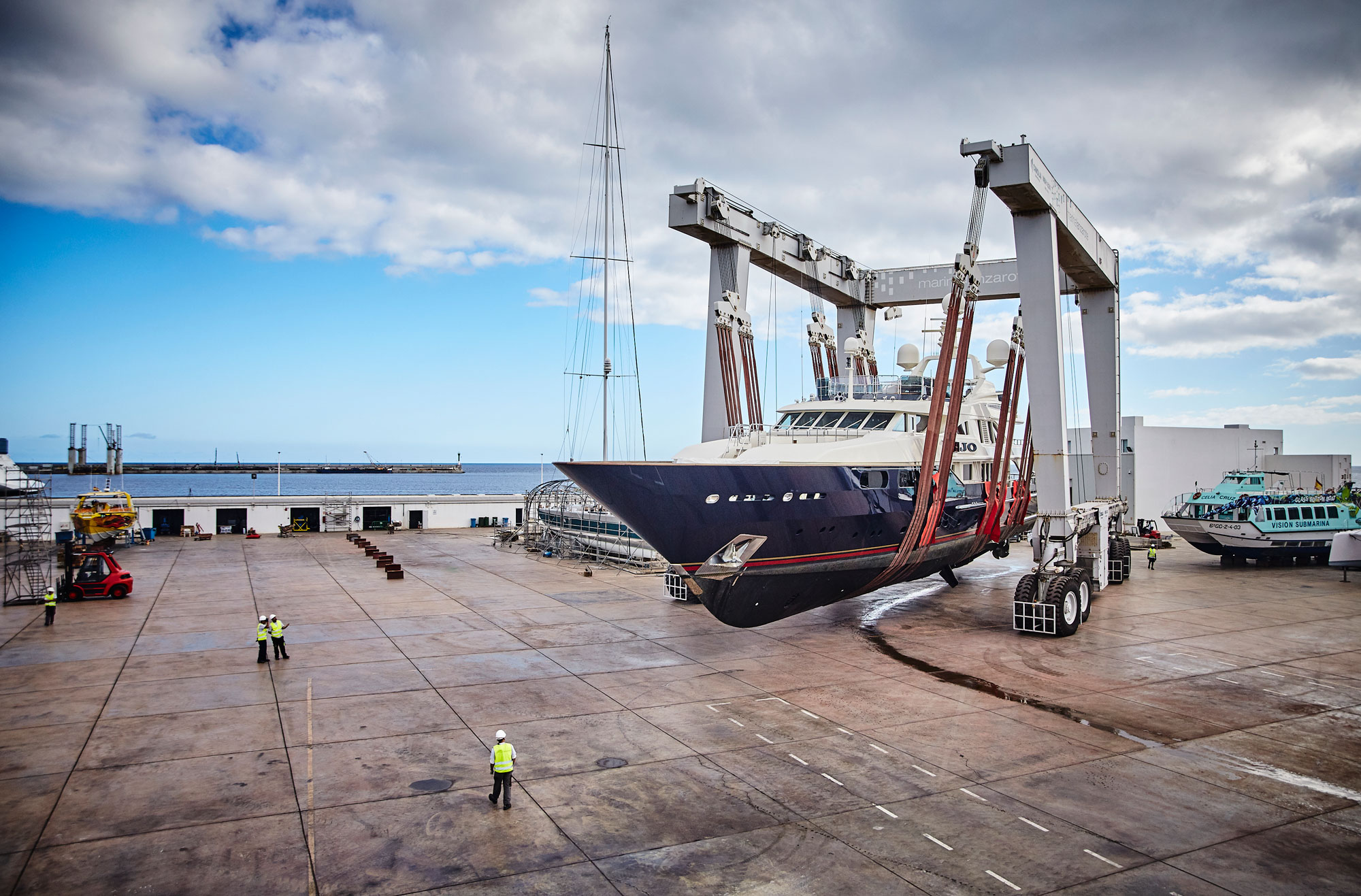 Very large blue and white yacht lifted out of water at Marina Lanzarote.