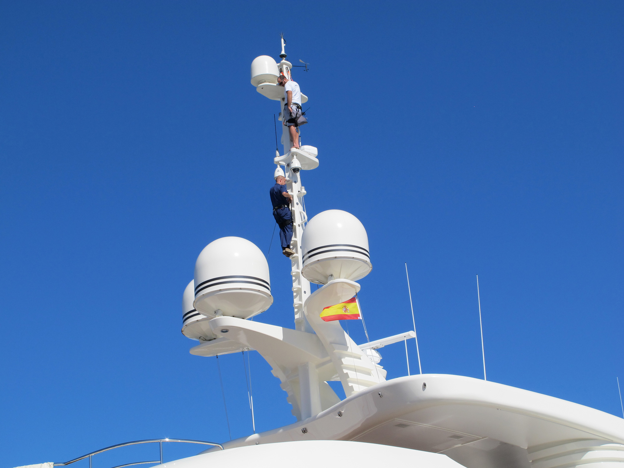 Two men working on the satellites of a superyacht on a beautiful blue sky day.