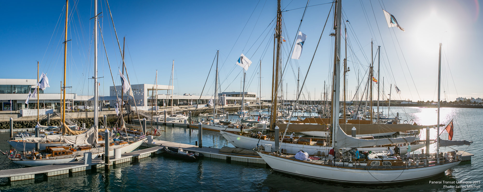 Large marina filled with white and wood sail boats in Lanzarote Island.