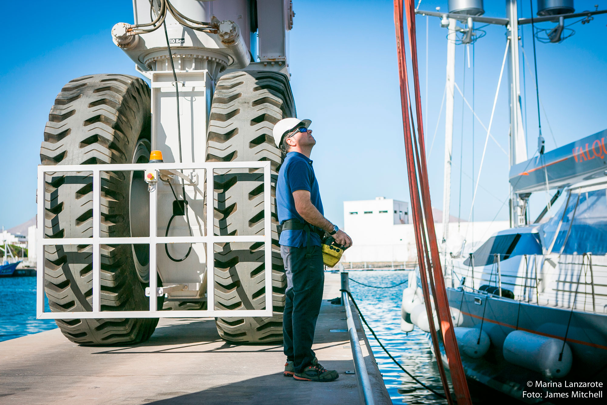 Man wearing a blue shirt and white hat near very large tires using a remote control to maneuver a yacht lift.