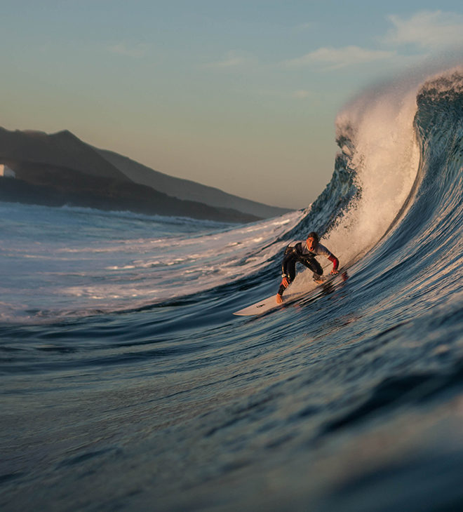 Man surfing the large waves in the clear blue waters by Lanzarote.