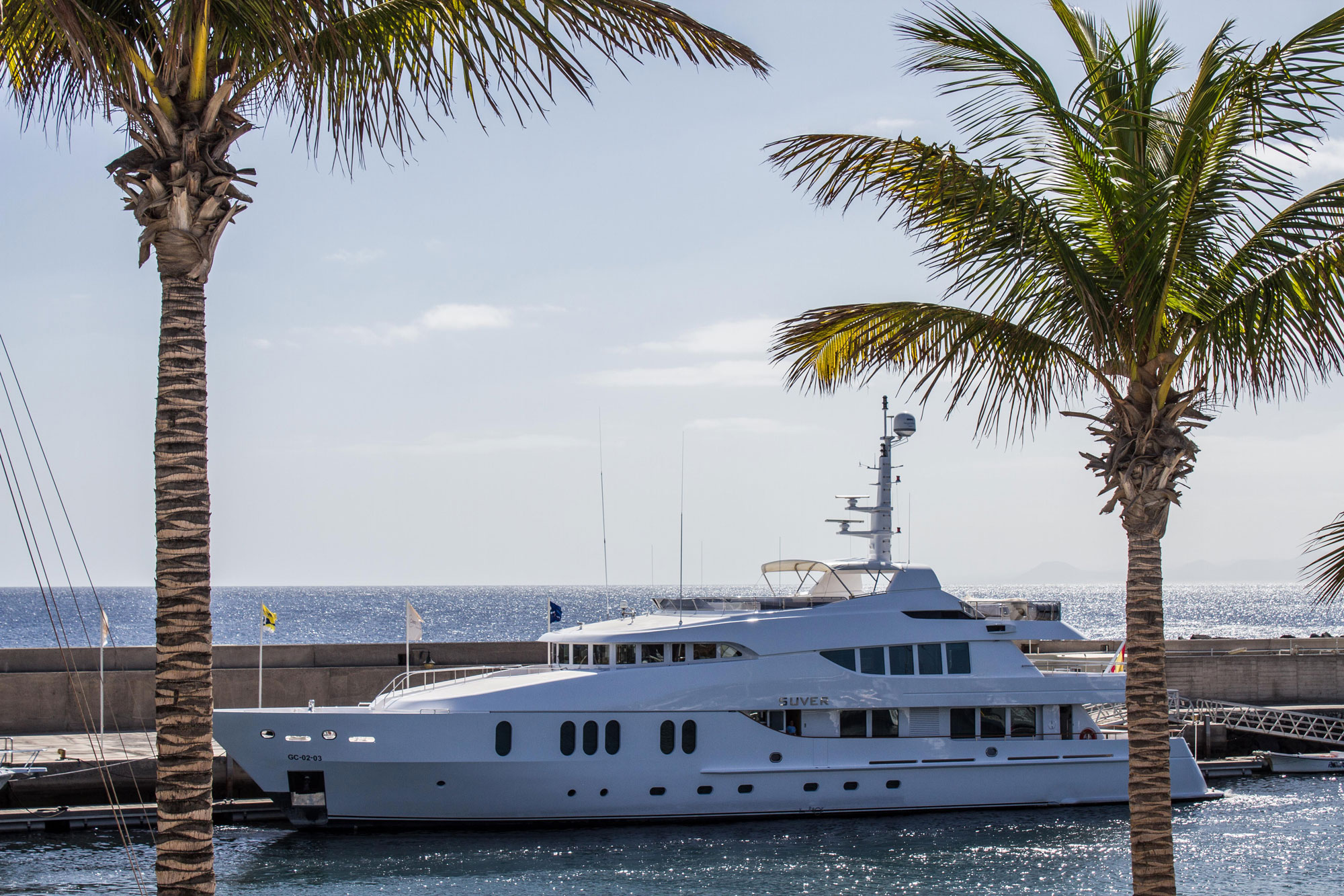 Yacht docked near two palm trees at the Canary Islands.
