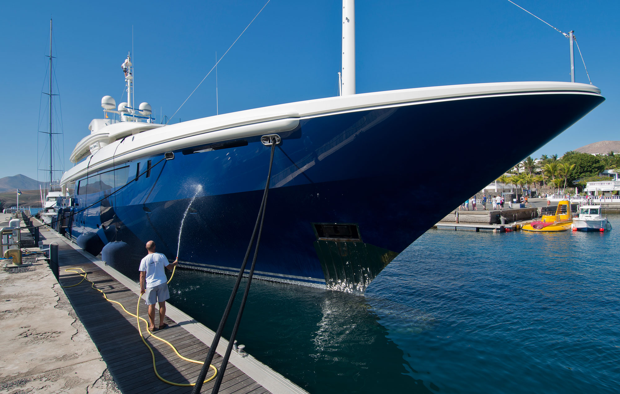 Man spraying a blue and white superyacht with water to clean the sides off.