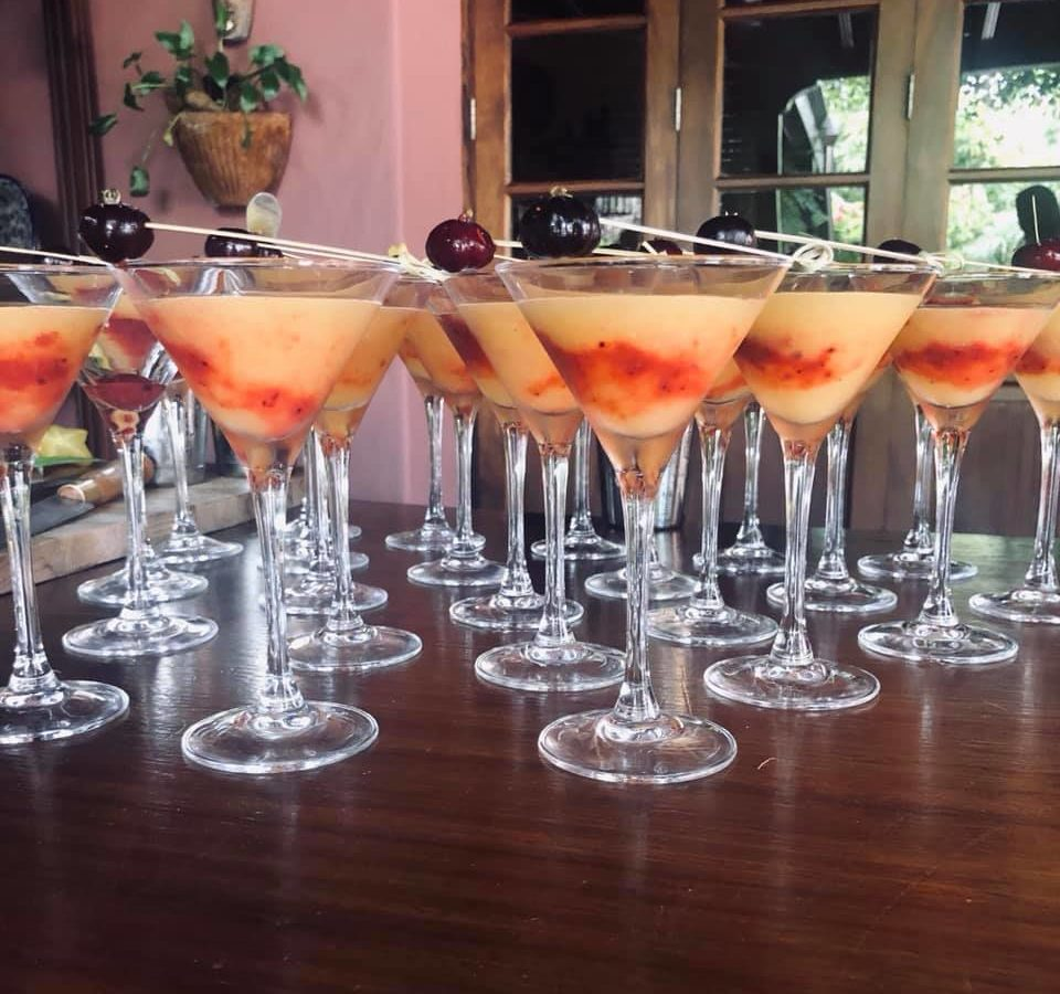 Several orange and red drinks in long stem glasses with cherry on top.