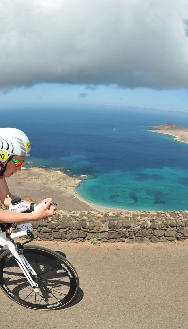 Man in cycling kit with racing helmet biking high above the blue waters and volcanic hills of Lanzarote.