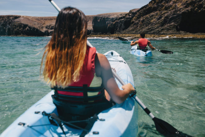 Woman and man wearing red life jackets while kayaking in the clear blue waters near the rocky shores of Lanzarote.