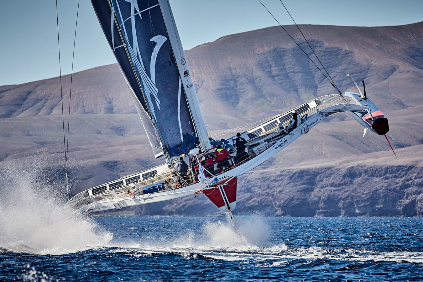Large white, red and blue sailboat racing in the RORC Transatlantic Race near Lanzarote.
