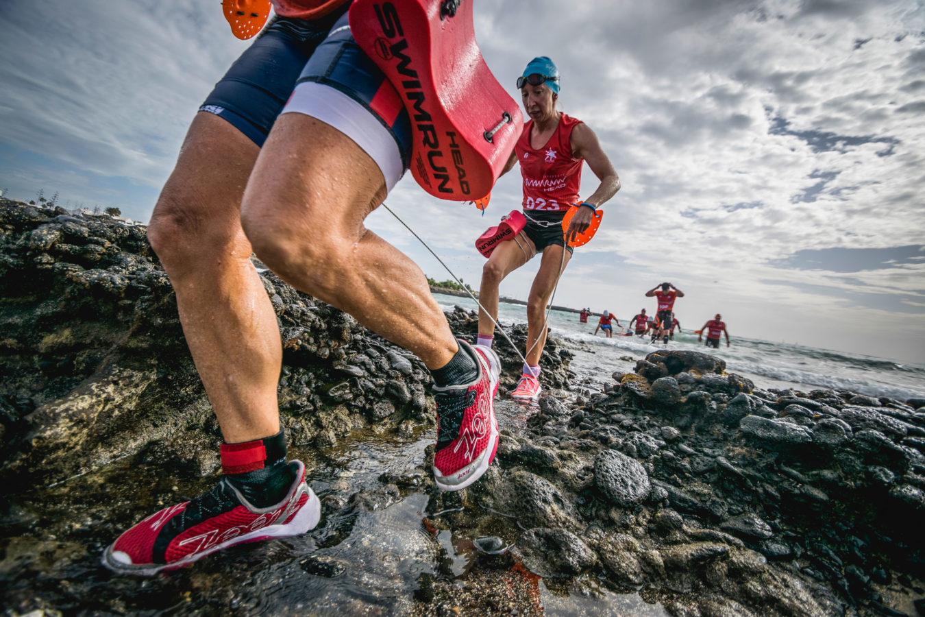 Swimmers transitioning from swim to run at the SwimRun Lanzarote race.