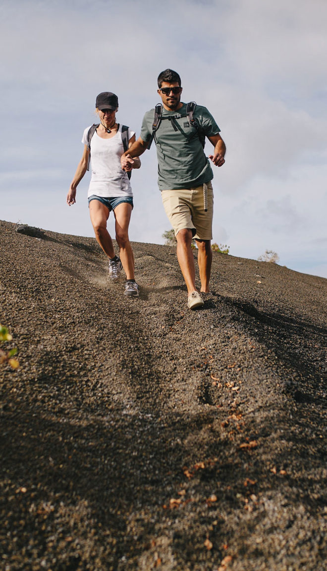 Couple hiking down a trail made of the black lava rock on Lanzarote Island.