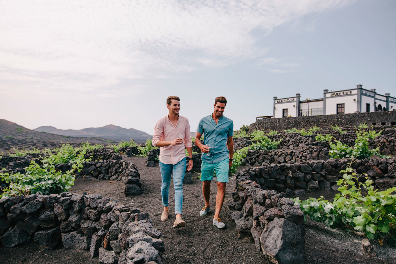 Two young men walking through the black lava rock at the vineyards on Lanzarote Island.