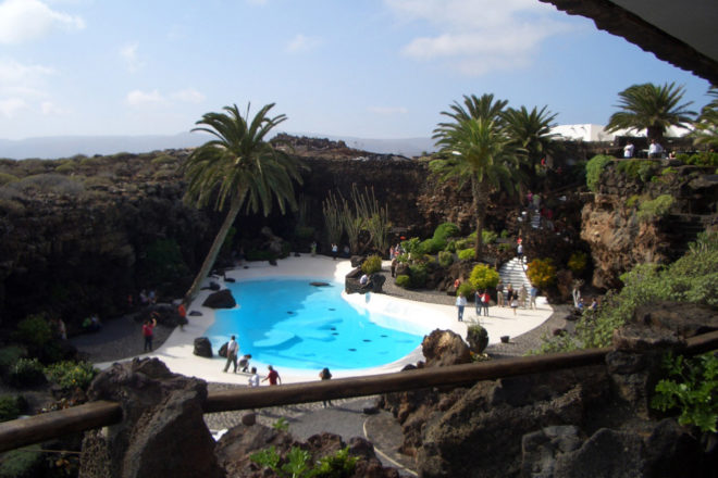 Visitors enjoying the blue pool amongst lava rocks and palm trees at Jameos.