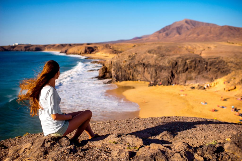Young woman sitting on cliff overlooking beach and coast of Lanzarote island.